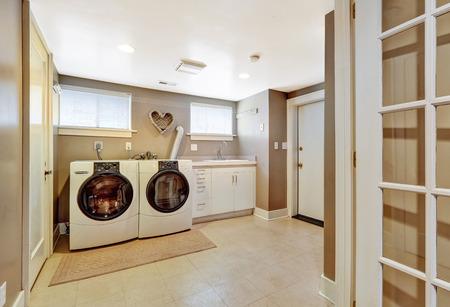 machine �   laver: Buanderie spacieuse avec carrelage et les murs gris clair. Meubl� avec des appareils modernes