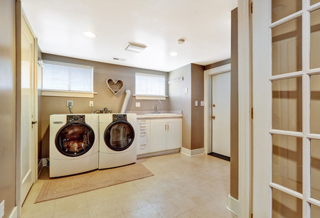 Spacious laundry room with tile floor and light grey walls. Furnished with modern appliances Stock fotó