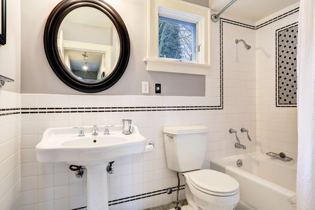 Bright bathroom interior with tile wall trim, white bath tub, toilet and washbasin cabinet Stock Photo