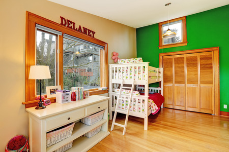 Bright kids room with contrast green wall. Furnished with loft bed and cabinet with storage baskets photo