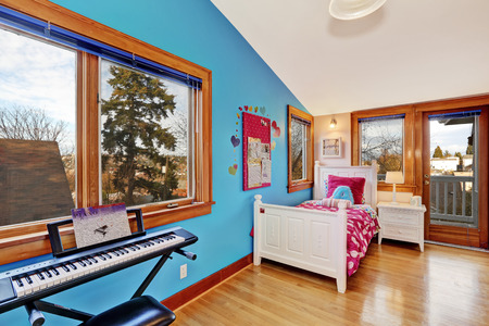 Bright young adult room with contrast blue wall and walkout deck. Furnished with white bed with nightstand and piano photo