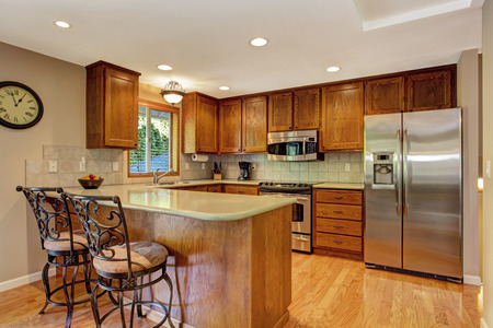 appliances: Kitchen room with steel appliances and antique stools