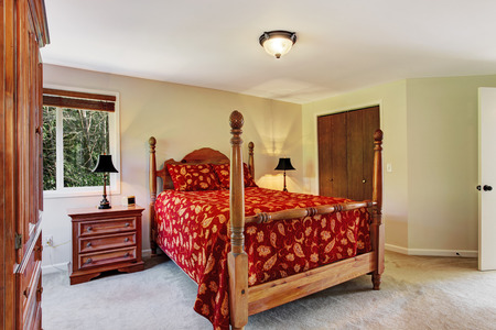 nightstand: Bright bedroom with carved wood furniture.  View of high pole bed, nightstand, wardrobe