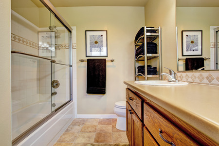 screened: Bathroom with wooden vanity cabinet and screened bath tub