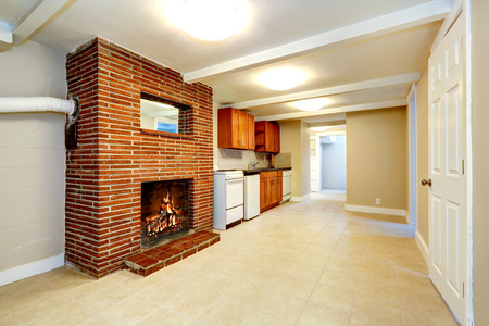 Empty basement room in soft ivory color with tile floor, kitchen cabinets and brick fireplace photo