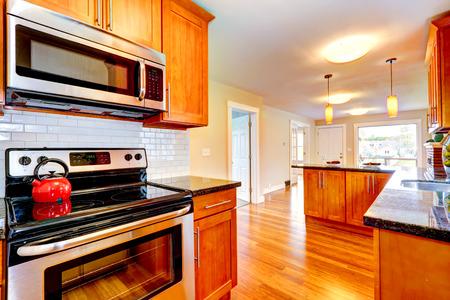 white trim: Bright kitchen room with black granite tops. View of steel stove and white tile back splash trim