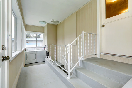 Bright hallway with stairs to basement. View of small laundry area photo