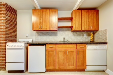 Honey kitchen cabinets with white appliances and tile back splash trim photo