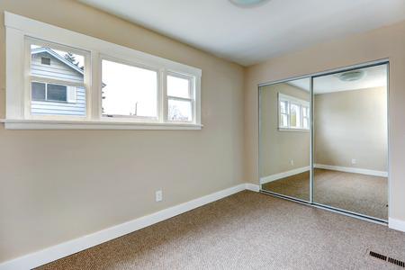 closet door: Bright empty bedroom with window and carpet floor. Room has mirror slide door closet