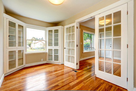Emtpy house with new hardwood floor and white french doors. View of entrance hallway and small office room Stockfoto