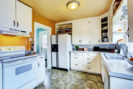 appliances: Kitchen interior in old house. View of white cabinets with white appliances.