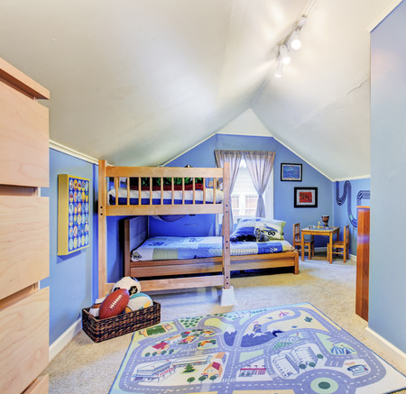 idea comfortable: Bright blue kids room with vaulted ceiling. Furnished with bunk bed and table set Stock Photo