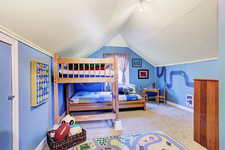 Bright blue kids room with vaulted ceiling. Furnished with bunk bed and table set photo