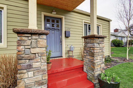front view: Entrance porch with black door and red stairs. Stone base trim columns