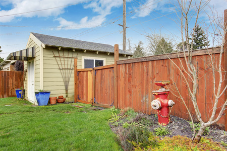fenced: Fenced backyard. View of shed with flower pots and wooden fence with gate