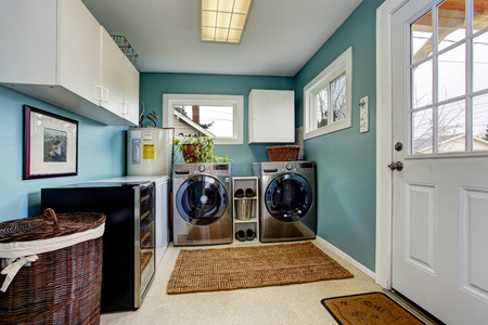 laundry room: Light blue laundry room with modern steel appliances and white cabinets