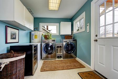 machine à laver: Lumière buanderie bleu avec des appareils modernes en acier et des armoires blanches