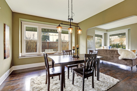 royalty free photo: Open floor plan. Dining area with dark brown dining table set and soft rug on hardwood floor