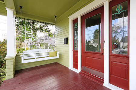Entrance porch in old house with contrast green and red walls. View of white wooden hanging swing Stockfoto