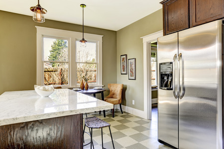 Olive tone kitchen room with steel refrigerator and marble top kitchen island Stock Photo