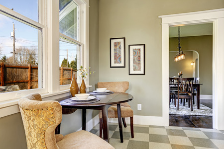dining table and chairs: Small dining area in kitchen room. View of served round table with brown chairs