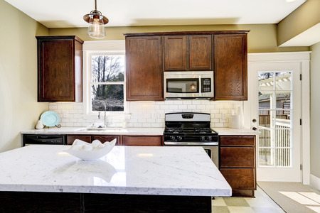top: Kitchen room with steel appliances, white tile back splash trim and marble top kitchen island