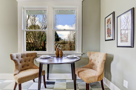 small table: Small dining area in kitchen room. View of served round table with brown chairs