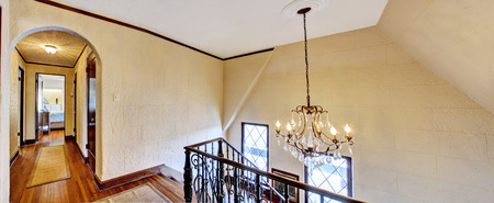 upstairs: Luxury house interior. Upstairs hallway with hardwood floor and stairs with iron railings
