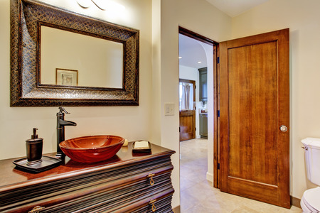 vessel sink: Bathroom interior in luxury house. View of rich bathroom vanity cabinet with vessel sink and mirror