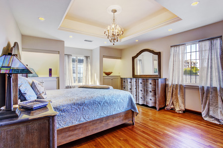 nightstands: Luxury bedroom with coffered ceiling and hardwood floor. Furnished with bed, nightstands and vanity cabinet
