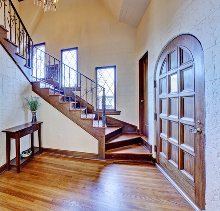 Beautiful entrance hallway in luxury house with wooden entrance door and staircase with iron railings photo