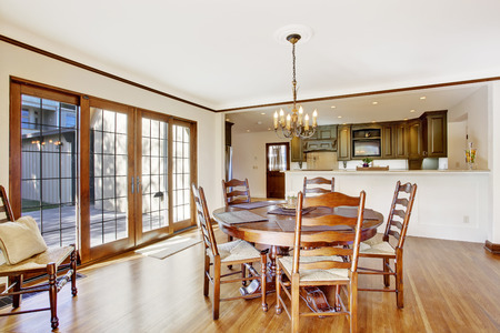 Bright dining room in luxury house with french door to walkout deck. View of kitchen room photo