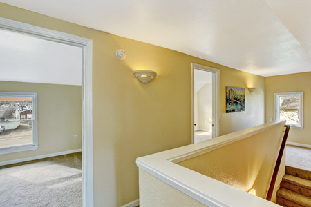 Light tones empty upstairs hallway with staircase photo