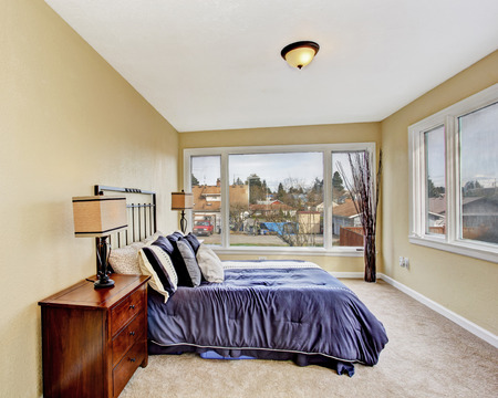 Bright ivory bedroom interior with carpet floor and queen size bed in purple