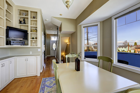 Dining room in light olive color with hardwood floor, blue rug and green dining table set photo