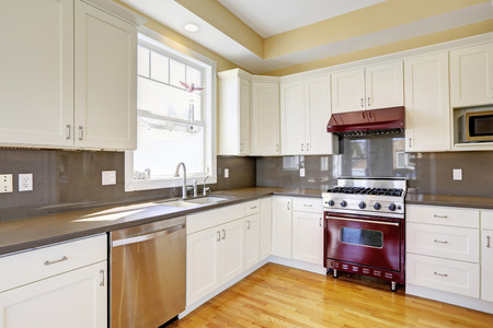 Bright kitchen room with hardwood floor, white cabinets, burgundy stove and grey counter tops