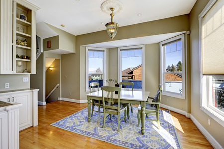 olive green: Dining room in light olive color with hardwood floor, blue rug and green dining table set