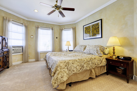nightstands: Light tones bedroom interior with queen size bed and dark brown nightstands
