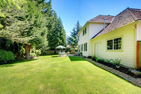 Achtertuin van grote gele huis met groen gras en een patio.