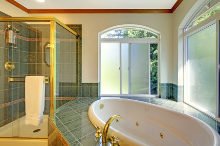bathroom sink: Large traditional bathroom with green tiles and jacuzzi.