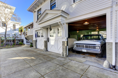 car in garage: House exterior. Three door garage with car and driveway