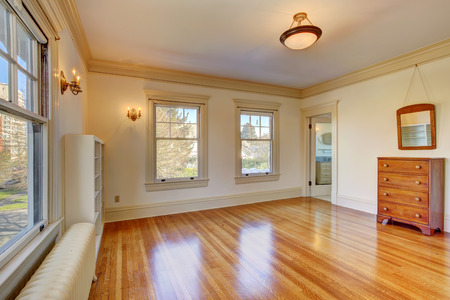 shiny floor: Empty clean room in soft ivory with shiny hardwood floor. View of wooden cabinet