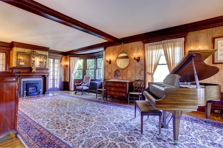 antique chair: Large living room with fireplace, antique furniture and grand piano in luxury house