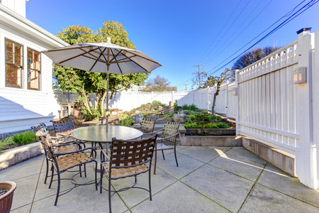 Backyard patio area with table, chairs and umbrella