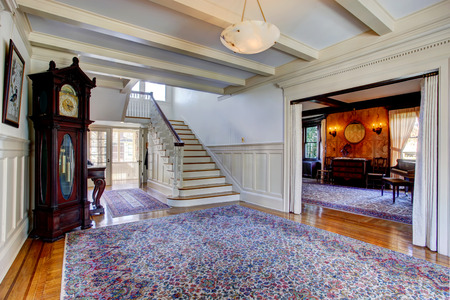 grandfather clock: Big luxury house. Entrance hallway with blue rug, grandfather clock and staircase view