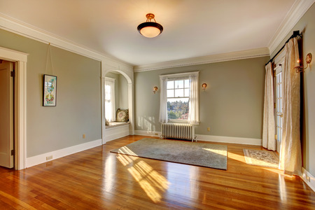 Empty clean room with shiny hardwood floor. View of cozy window bench with pillows