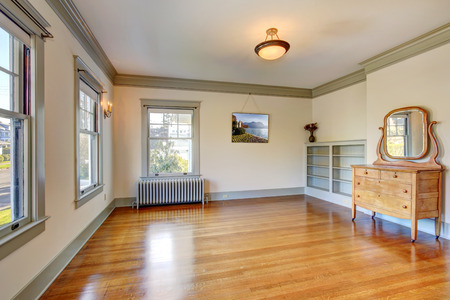 shiny floor: Empty clean room in soft ivory with shiny hardwood floor. View of wooden vanity cabinet Stock Photo