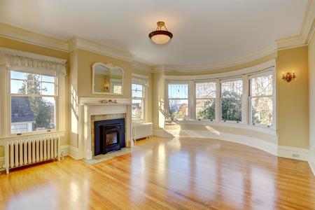 shiny floor: Bright empty living room with fireplace, shiny hardwood floor and round window