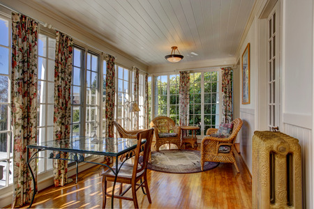 sunroom: Bright sunroom with french windows. Furnished with wicker table and chairs and glass top table