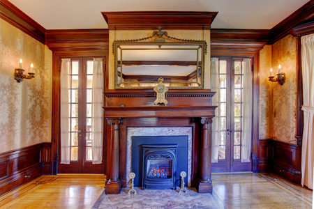 antique: Luxuriant fireplace with wooden columns, mirror and antique clock